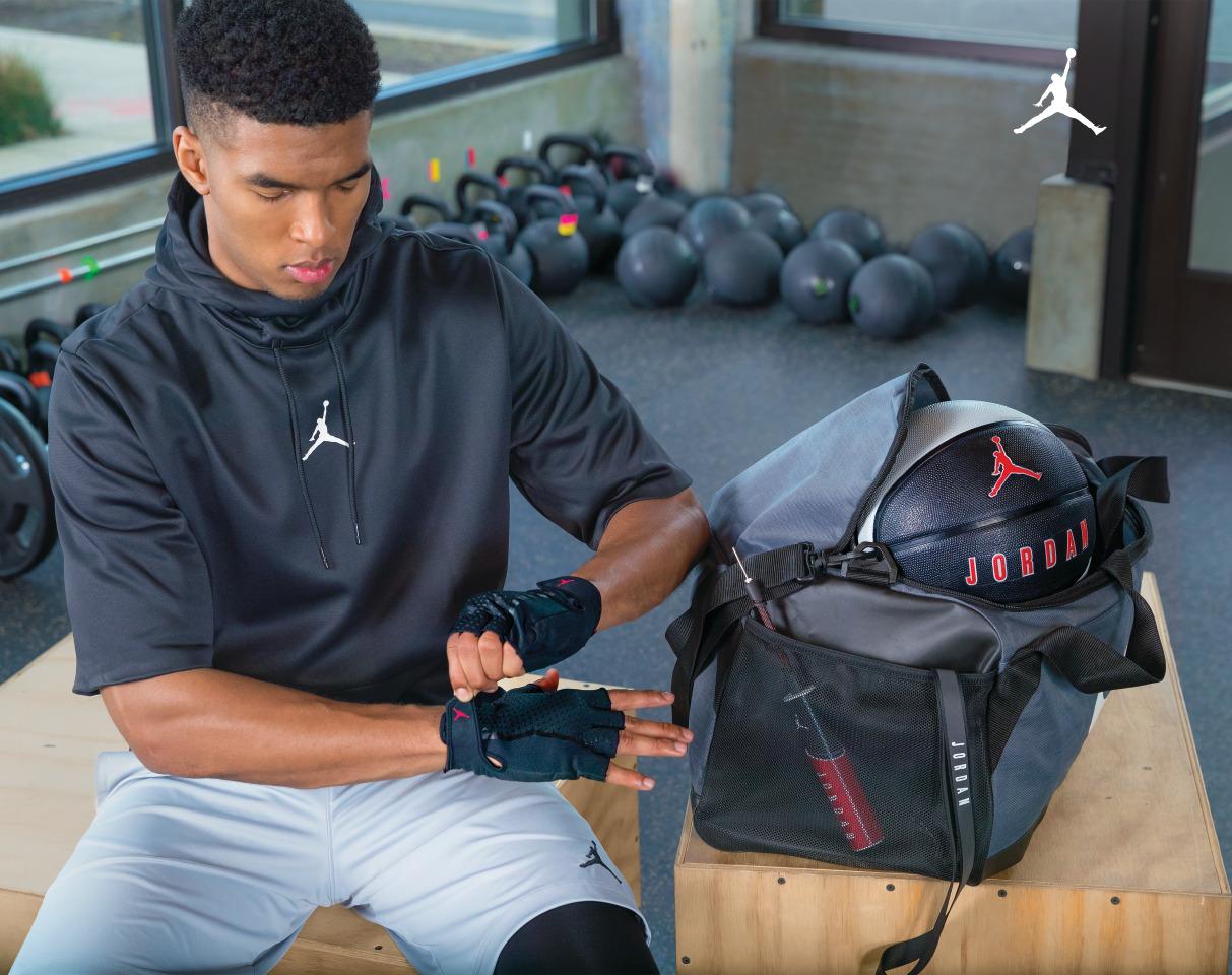 Deportista sentado en el gimnasio poniéndose un guante de Jordan