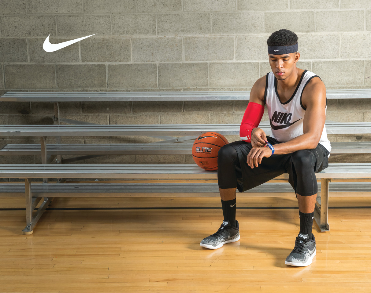 An athlete sitting on a bench at the gym wearing a complete Nike outfit