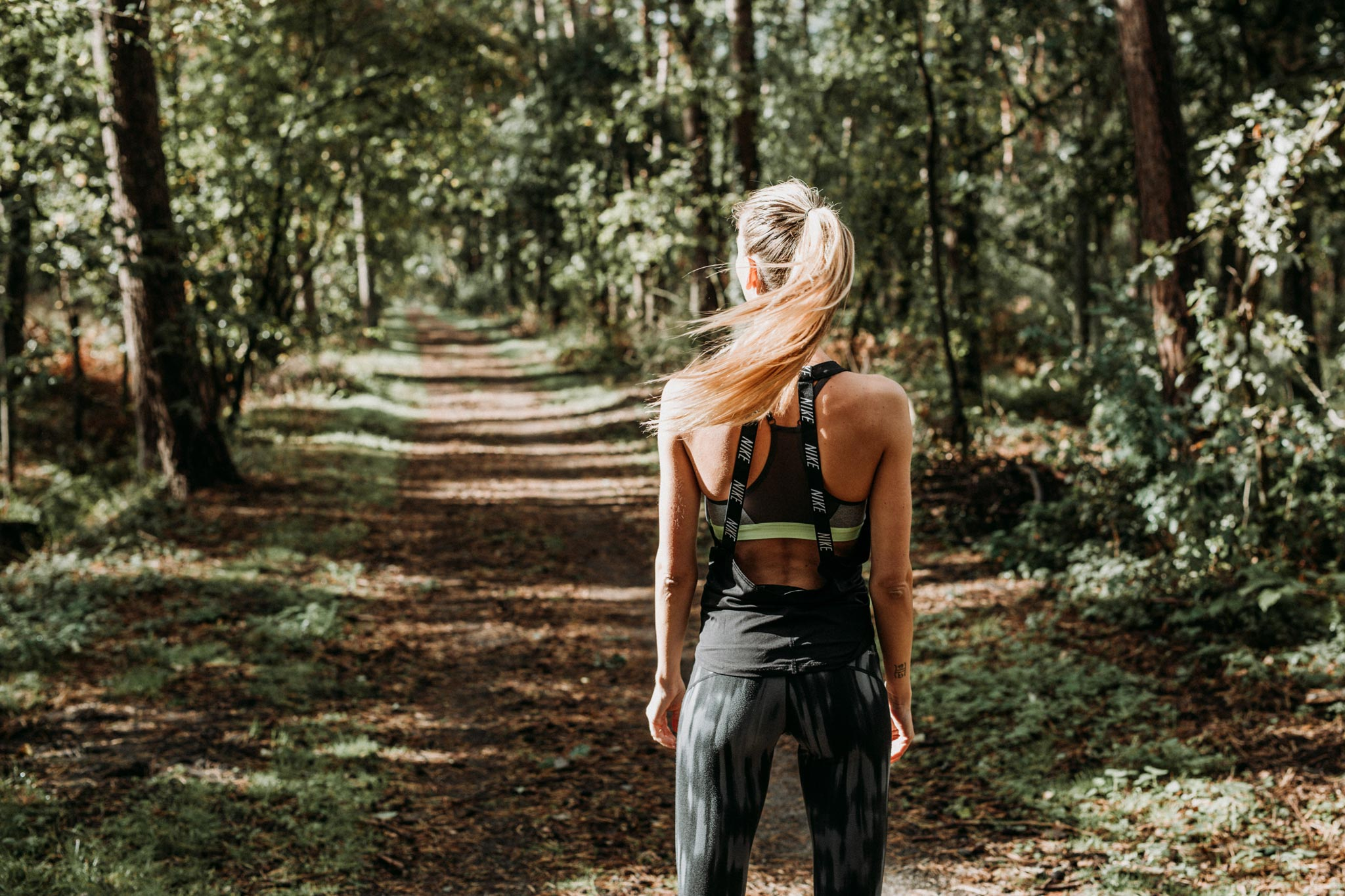 Female athlete running on an outdoor trail in the woods wearing a Nike outfit