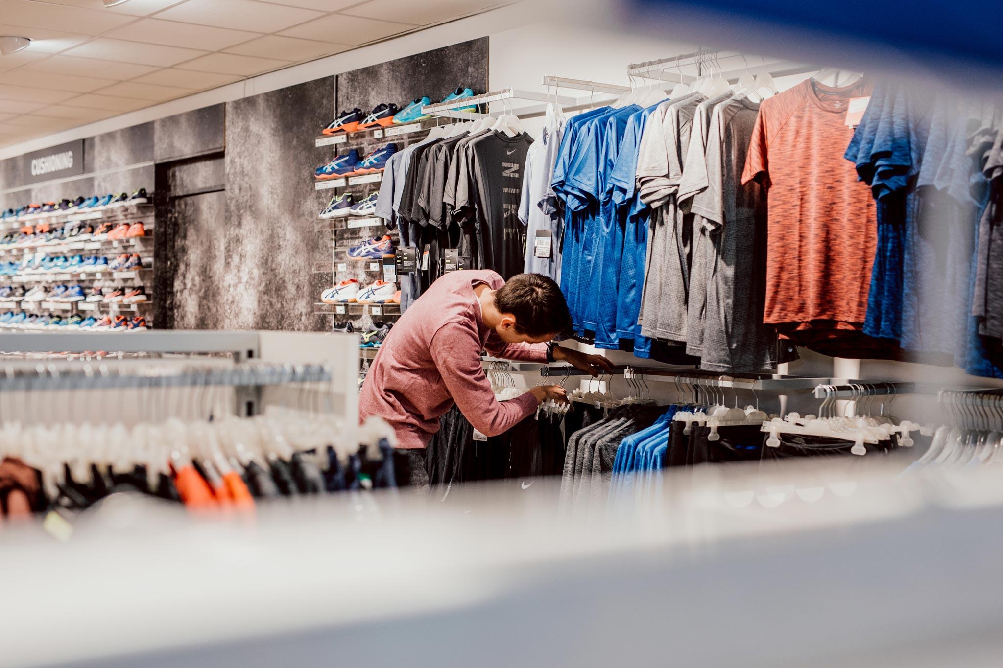 Un client et un vendeur discutant d'un sac Converse dans un magasin approvisionné par All Sport